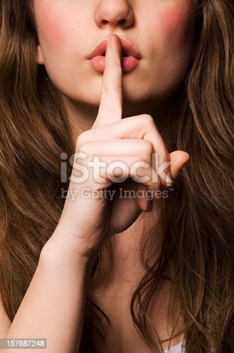 Young woman gesturing for being quiet