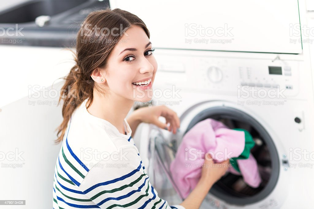 Woman Putting her Laundry into a Washing Machine stock photo