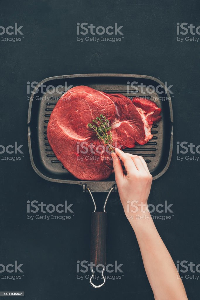 woman putting herb onto raw steak on grill pan stock photo