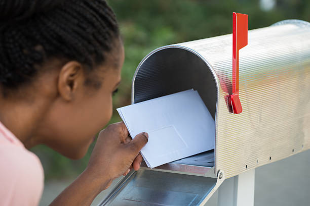 Woman Putting Letter In Mailbox - Photo