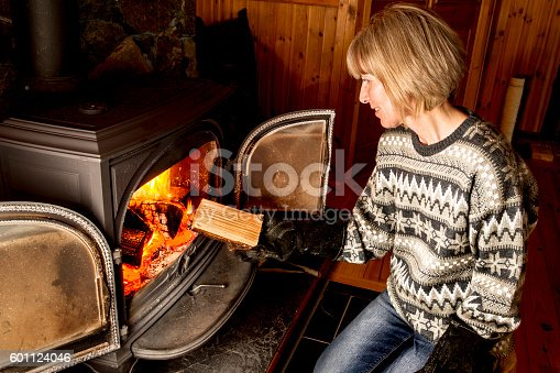Woman putting wood on a wood burning stove. AdobeRGB colorspace.