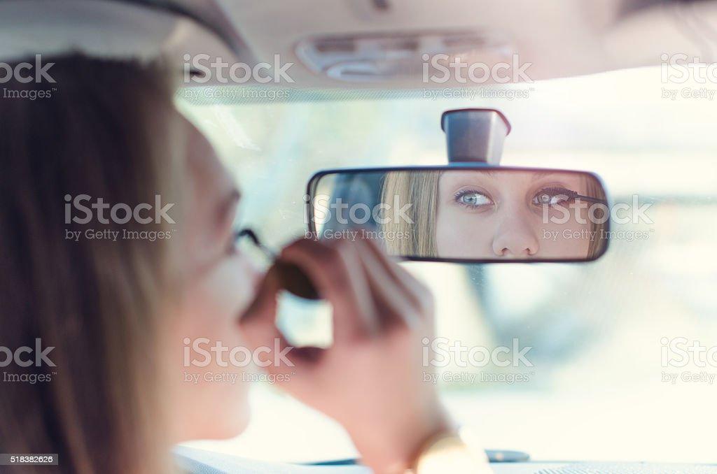Mulher colocando maquiagem em um carro. - foto de acervo