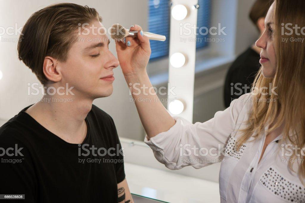 Woman putting makeup on man zbiór zdjęć royalty-free