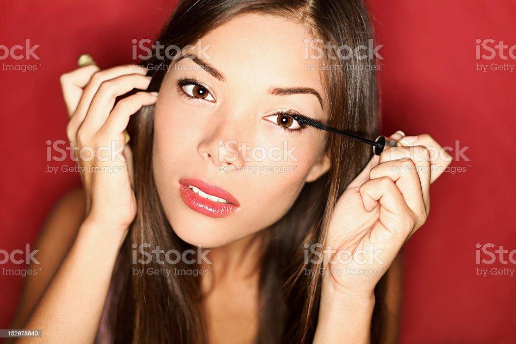 Woman putting mascara makeup stock photo