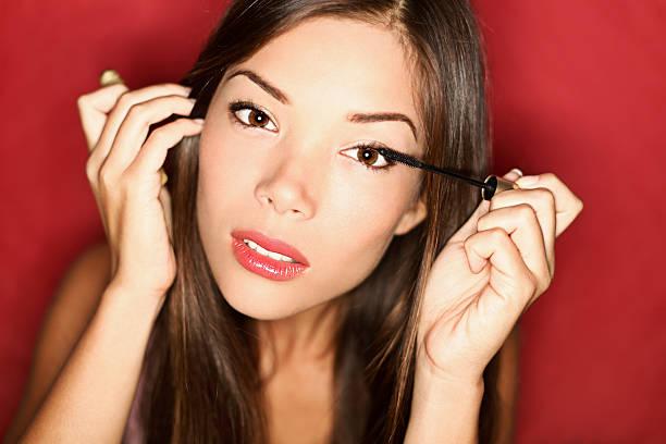 make-up frau putting mascara - anzieh nacht stock-fotos und bilder