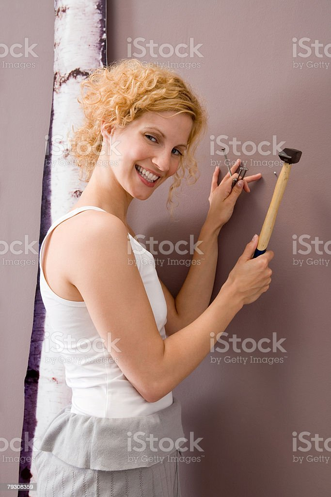 Woman putting nails in wall royalty-free 스톡 사진