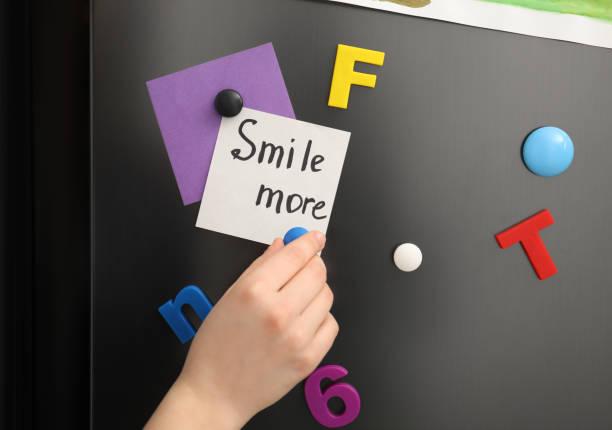 woman putting note with phrase smile more on refrigerator door, closeup - sticker fridge hình ảnh sẵn có, bức ảnh & hình ảnh trả phí bản quyền một lần