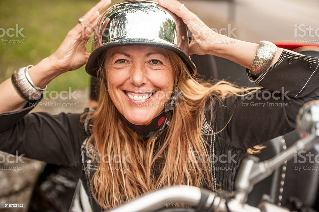 Woman Putting on a Vintage-style Biker's Helmet stock photo