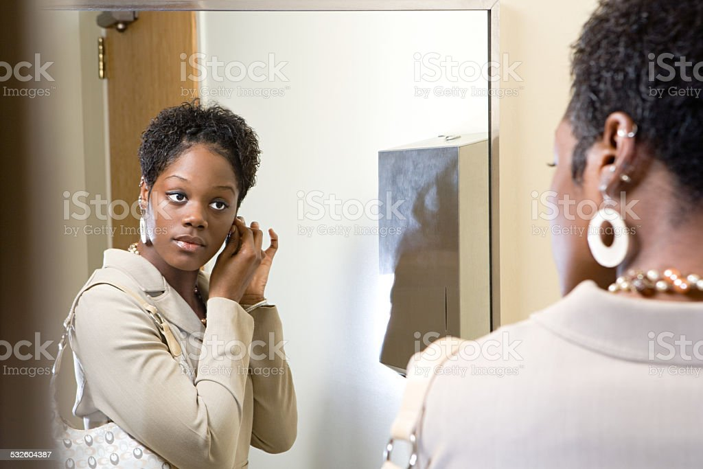 Woman putting on earrings stock photo