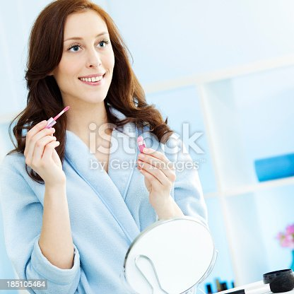 109721176istockphoto Woman Putting on lipstick in a bathroom 185105464