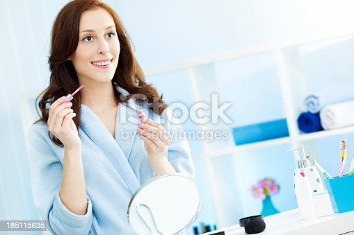 Beautiful Young Woman in bathrobe putting on lipstick in bathroom, preparing for new day