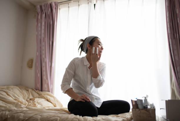 メイクアップを置く女性 - 独身の若者 ストックフォトと画像