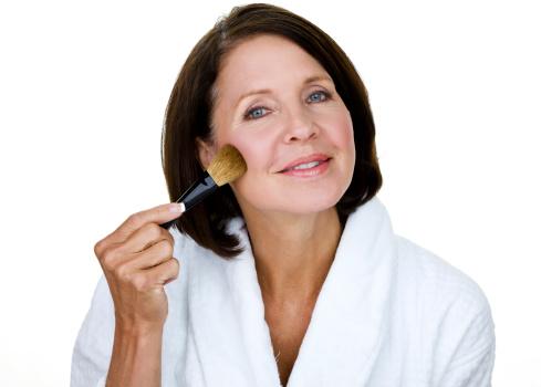 Beautiful older woman wearing a bathrobe and applying makeup