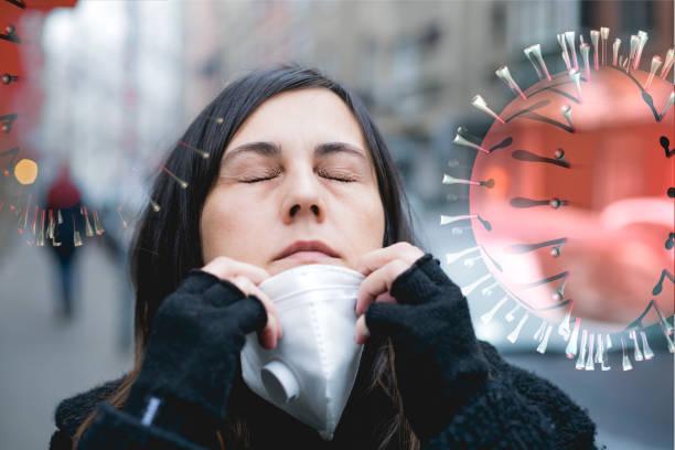 mujer poniéndose máscara para protegerse de los virus - foto de stock