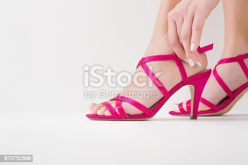 istock Woman putting on pink high heels sandals. Empty place for a text. 870752896