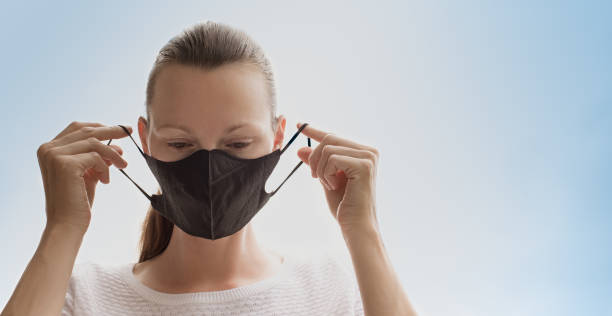 Woman putting on protective face mask. stock photo