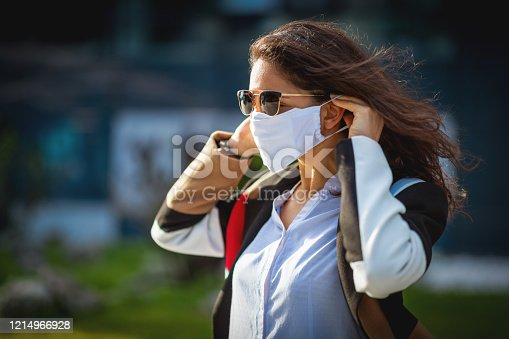 Serious woman putting on protective face mask, walking through city streets