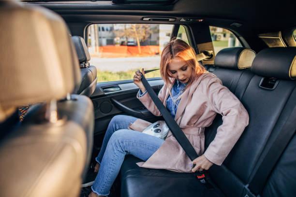 Woman putting on seat belt stock photo