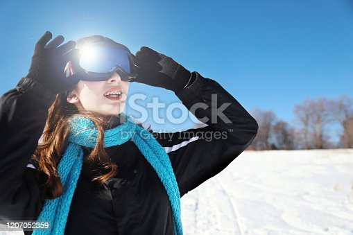 Young woman putting on ski goggles in the mountain