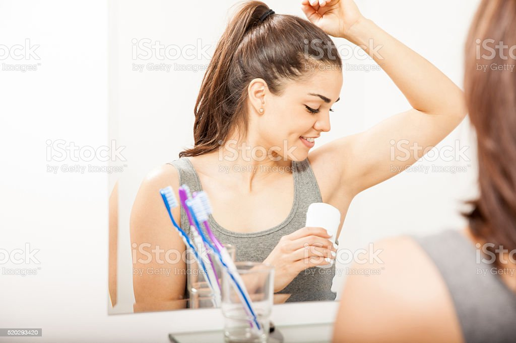 Woman putting on some deodorant stock photo