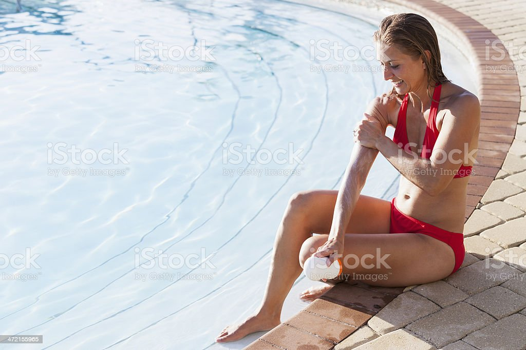 Woman putting on sunscreen stock photo
