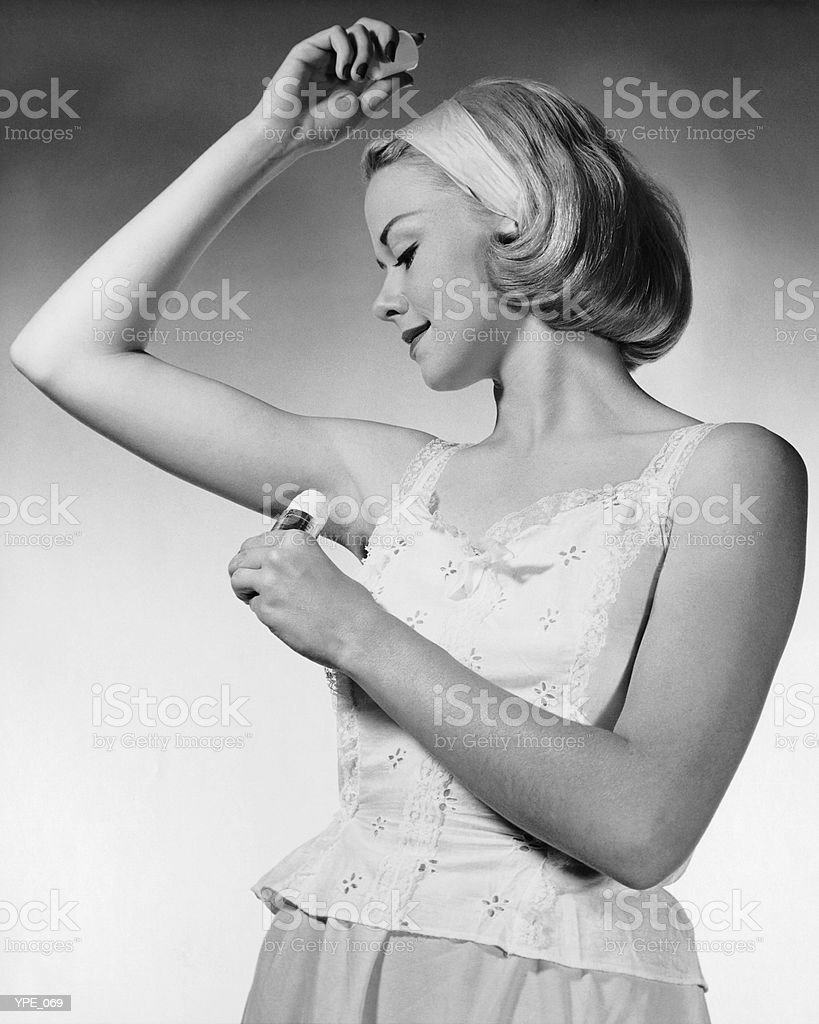 Woman putting on underarm deodorant royalty-free stock photo