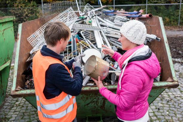 Frau setzt Altmetall in Container, um recycelt zu werden – Foto