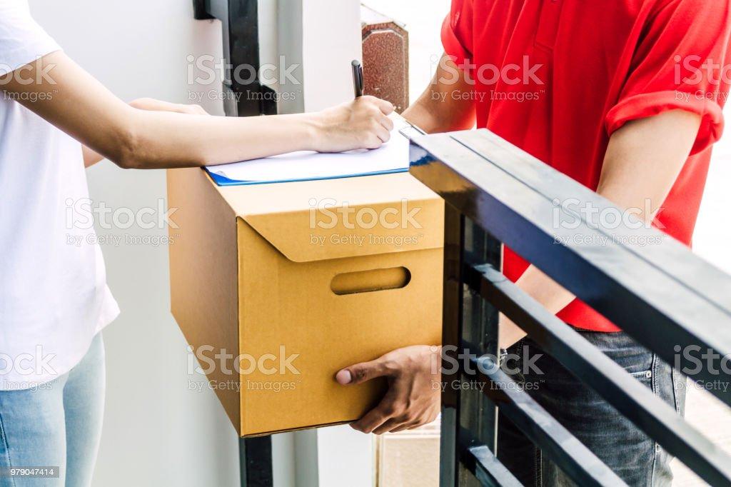 赤 uniform.courier サービス概念の配達人と受信パッケージに段ボール箱でクリップボードに署名を入れて女性 - ウエストのロイヤリティフリーストックフォト