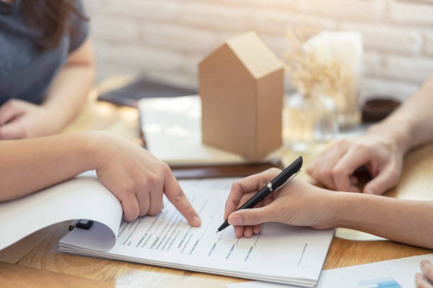 woman putting signature on document contract, real estate purchase, success business contract deals with sale represent. woman putting signature on document contract, real estate purchase, success business contract deals with sale represent. mortgage loan stock pictures, royalty-free photos & images