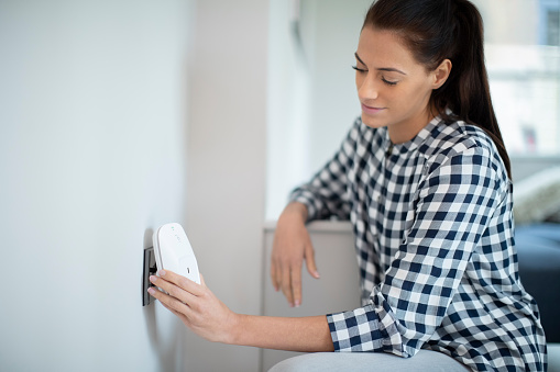 Woman Putting Smart Plug Into Power Socket At Home Stock Photo - Download Image Now