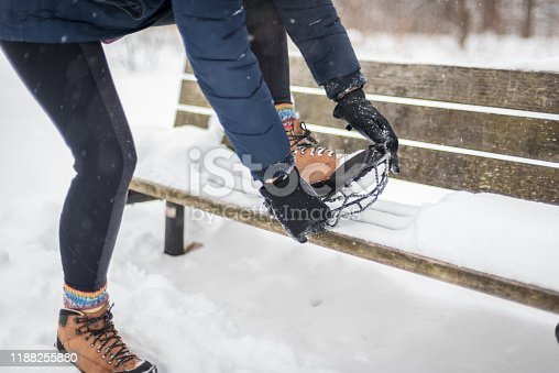 woman getting ready to take hike in snow fixing cleat onto boots