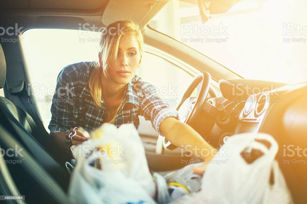 Woman putting some plastic bags into her car. stock photo