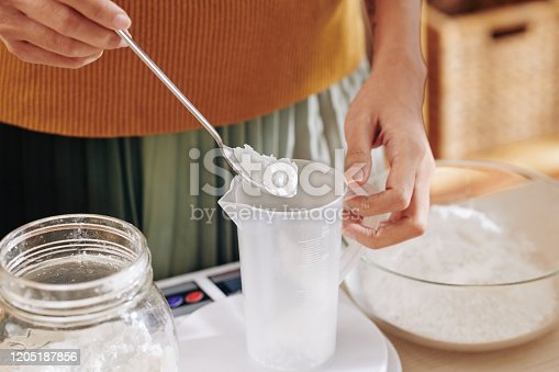 Close-up image of woman putting spoon of lye in plastic jar when making soap at home