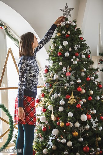 Young woman is decorating a large family Christmas tree in the living room. She is putting a star on top of a Christmas tree.