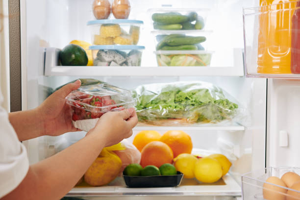 Woman putting strawberries in fridge stock photo