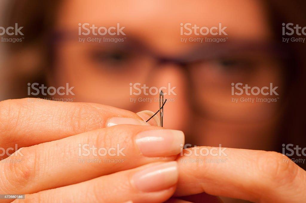 Woman putting string through needle stock photo