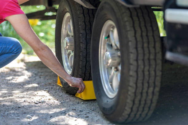 Woman Putting Tire Blocks on Camper Trailer stock photo