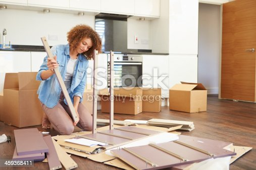 459373065 istock photo Woman Putting Together Self Assembly Furniture In New Home 459368411