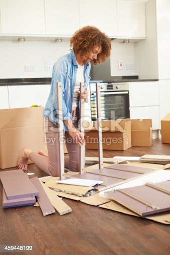 459373065 istock photo Woman Putting Together Self Assembly Furniture In New Home 459448199