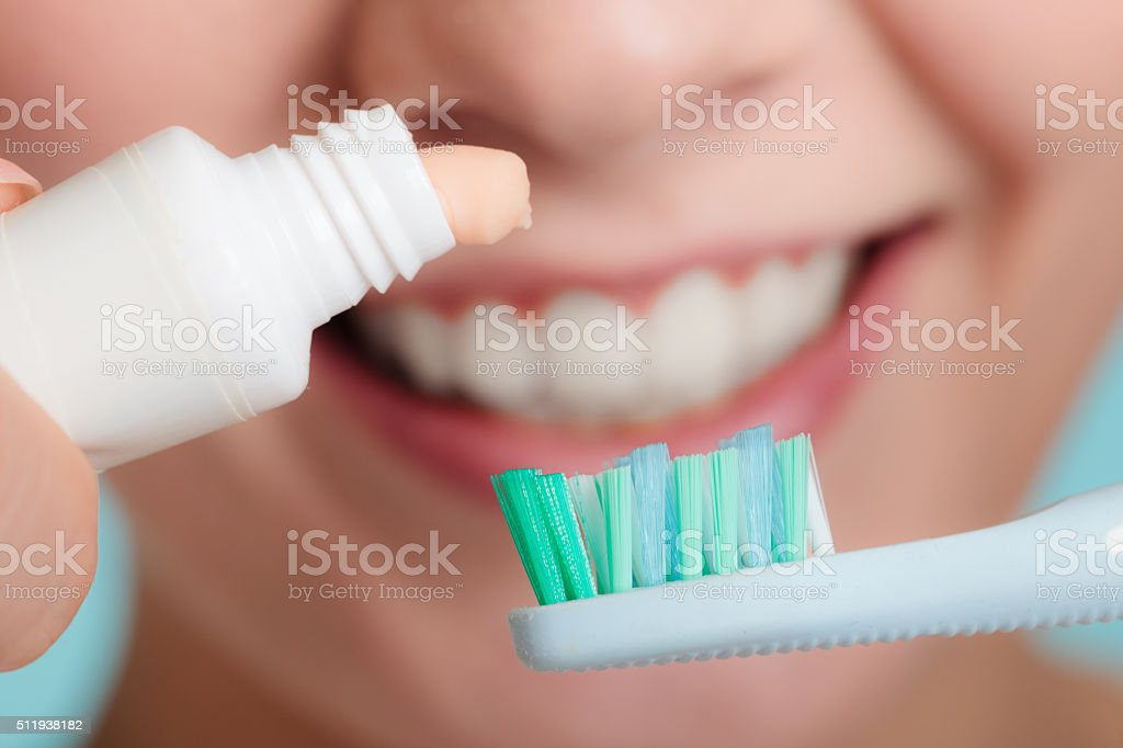 Woman putting toothpaste on toothbrush stock photo
