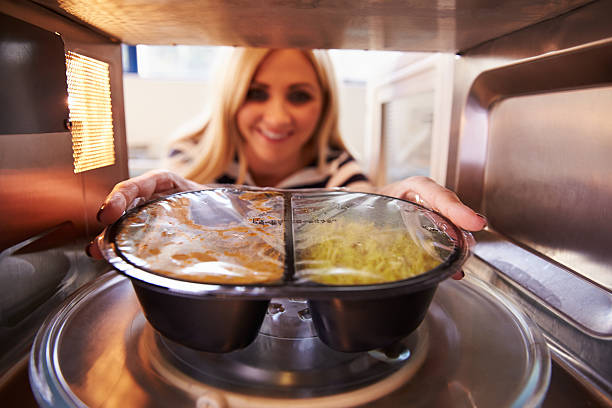 woman putting tv dinner into microwave oven to cook - gemaksvoedsel stockfoto's en -beelden