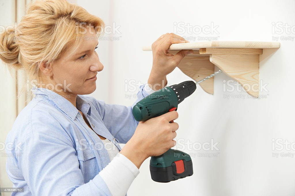 Woman Putting Up Wooden Shelf At Home Using Cordless Drill stock photo
