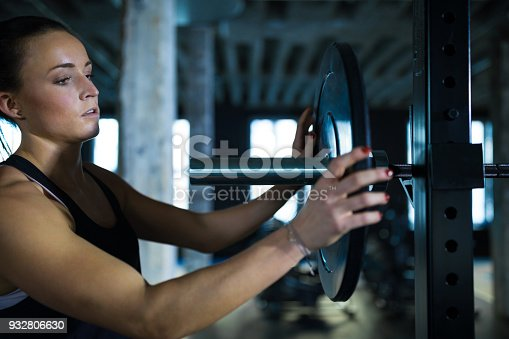 Woman loading weight plates on barbell rack. Determined female athlete exercising in gym. She is in sportswear.