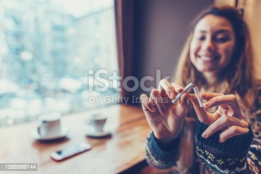 Quit smoking concept with young smiling woman sitting at the café and tearing her cigarette