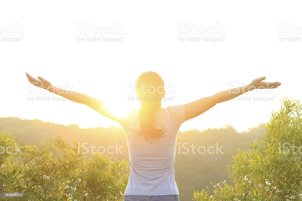 woman raised arms to sunrise stock photo