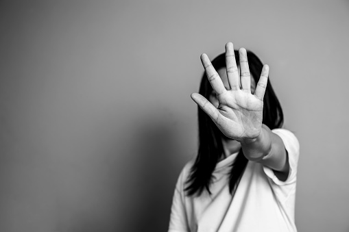 istock woman raised her hand for dissuade, campaign stop violence against women. Asian woman raised her hand for dissuade with copy space, black and white color 1001313596