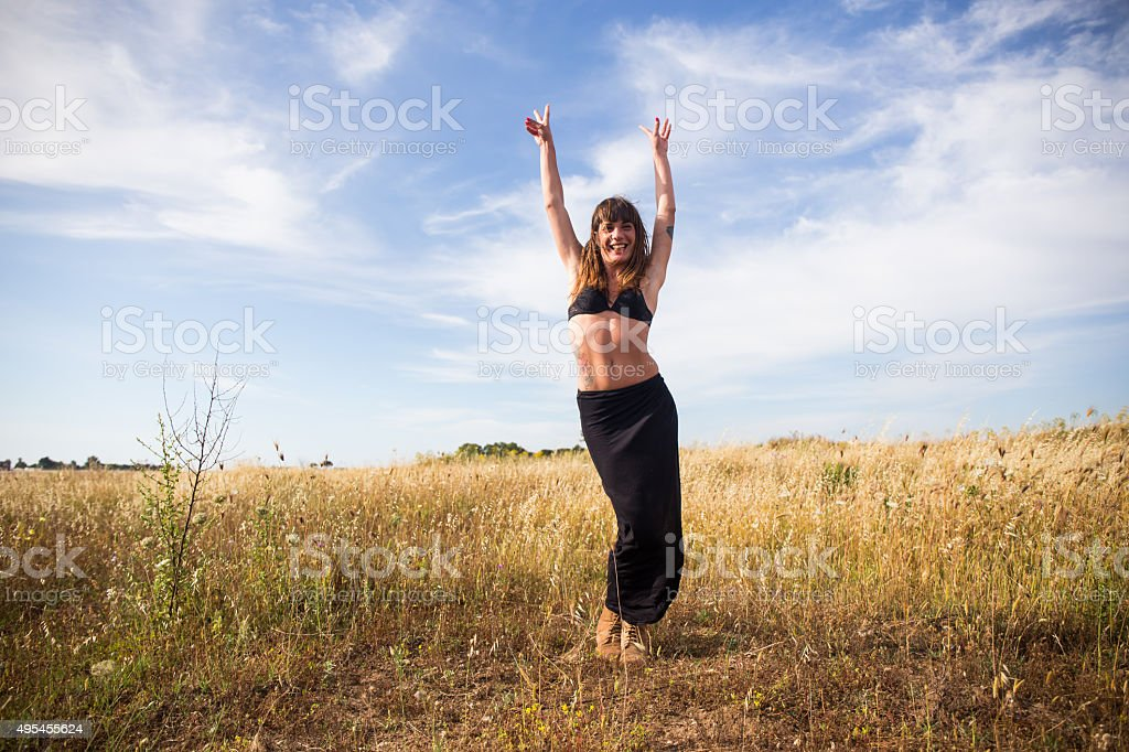 Woman raises her hands to the sky and smiles stock photo