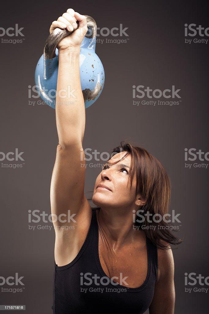 Donna alzando un blu Kettle Bell - foto stock