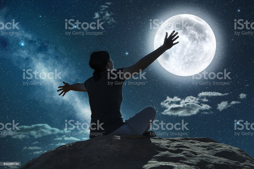 woman raising arms in the moonlight stock photo