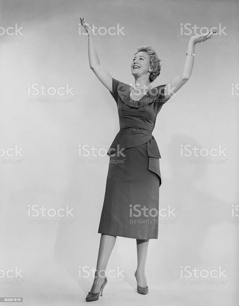 Woman raising arms, studio shot 免版稅 stock photo